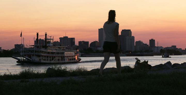 A woman walks atop an earthen levee on the Mississippi River in the Lower 9thWard as the Steamboat Natchez passes in Au