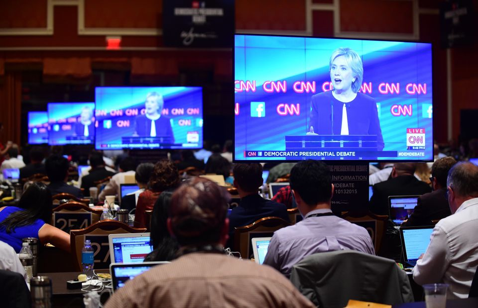 Presidential hopeful Hillary Clinton appears on screens in the press room as journalists cover the Democratic presidential de