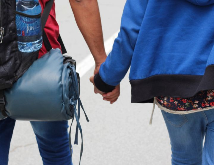 Dozkin and Serwan hold hands as they walk toward the Serbia-Hungary border on Aug. 23. They have a long walk ahead of them, f