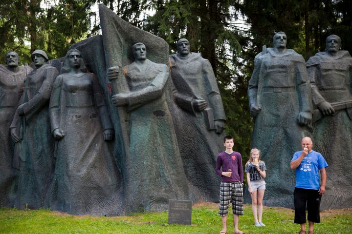 A family awkwardly poses for a photo by a large Soviet soldier statue.