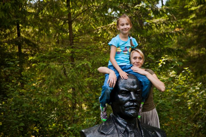 Mother and daughter playfully pose atop Lenin's head.