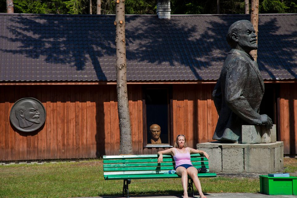 A woman tans under the watchful eye of Lenin.