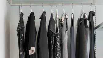 modern closet with row of black dress