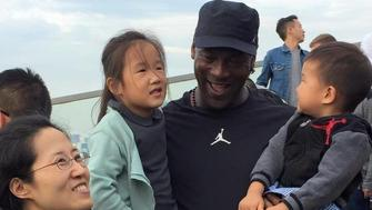 Michael Jordan shares a laugh with the children of a late Air Jordan employee in Shanghai.