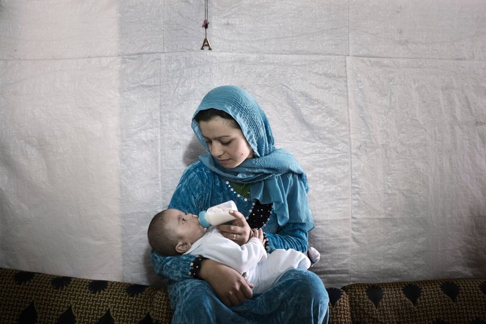 Syrian refugee Samira, 14, feeds her 7-month-old son inside their tent shelter in Rawda, Bekaa Valley.