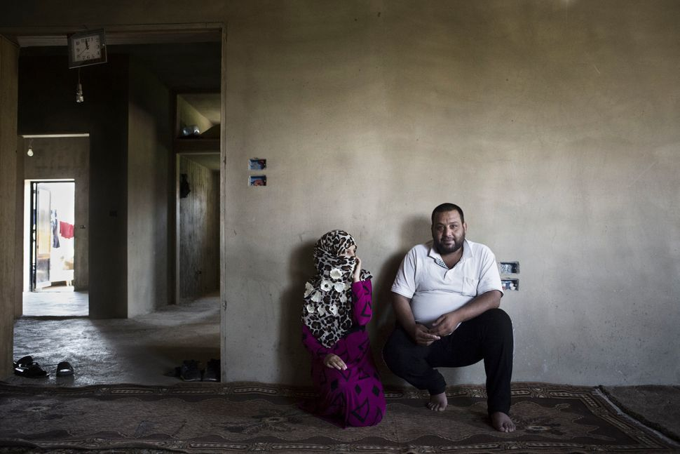 Nour, 13, sits with her 27-year-old husband inside their dwelling in Jeb Janine, Bekaa Valley. Nour and her family, who are r