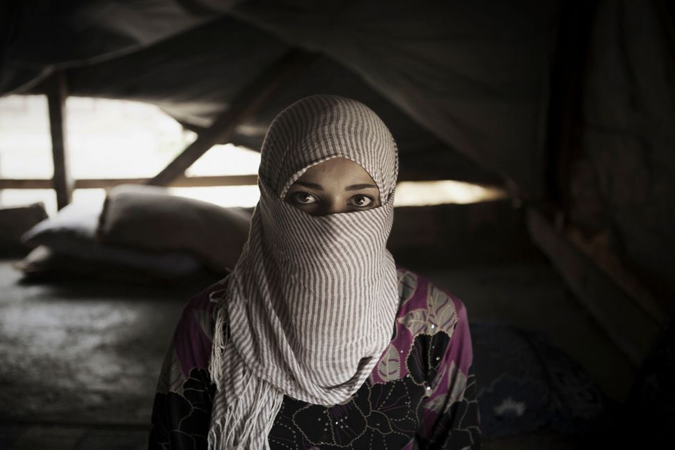 Syrian refugee Waad, 13, stands inside her tent shelter in Bekaa Valley. Waad, whose father forced her to marry a man she did