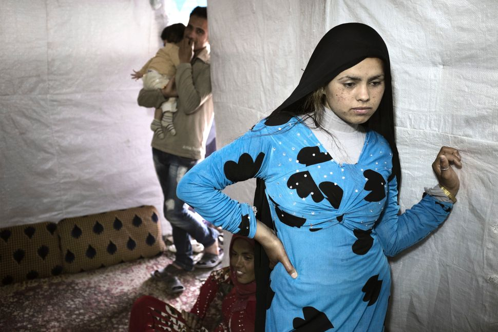 Syrian refugee Hened Al Ahmad, 14, stands inside a tent shelter in Rawda, Bekaa Valley. Hened, who got married 18 months ago,