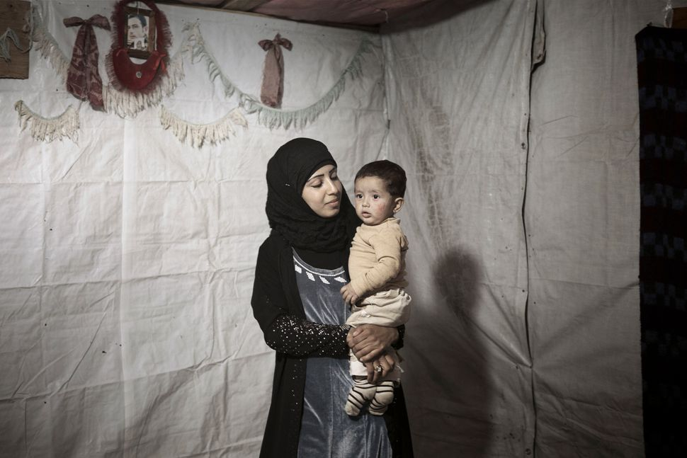 Syrian refugee Amina, 14, holds her young son inside their tent shelter in Bekaa Valley.
