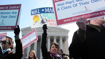 WASHINGTON, DC - MARCH 29:  Activist Eva Yung (C) of Alliance for Justice holds a sign during a rally in front of the U.S. Supreme Court March 29, 2011 in Washington, DC. The Supreme Court has started to hear arguments on whether Wal-Mart, the world's biggest retailer, systematically discriminated against women in stores across America and should go forward and proceed as a class action suit. (Photo by Alex Wong/Getty Images)