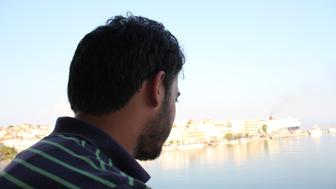 Taha, a former Free Syrian Army fighter in Homs who rescued french journalist Edith Bouvier in 2012, looks out over the harbor in Mytilene on Greece's Lesvos island, Aug. 16.