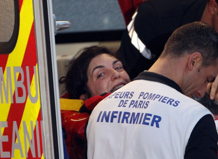 French journalist Edith Bouvier smiles as firefighters carry her into an ambulance after the plane carrying her and French ph