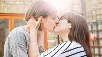 lesbian couple kissing in garden.