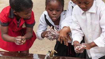 JOHANNESBURG, SOUTH AFRICA - OCTOBER 15: Children learn to wash their hands with Lifebuoy soap, at Margeret Gwele Primary School, Soweto,  on October 15, 2012 in Johannesburg, South Africa. Celebrated in over 100 countries, Global Handwashing Day is an annual awareness day which aims to put the global spotlight on handwashing with soap as a lifesaving habit. (Photo by Greg Marinovich/Getty Images for Unilever)