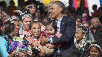 US President Barack Obama (C) holds a child as he poses with Native American performers during the Cannon Ball Flag Day Celebration in Cannon Ball, North Dakota, June 13, 2014.       AFP PHOTO / Jim WATSON        (Photo credit should read JIM WATSON/AFP/Getty Images)