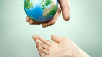 mans hand holding model globe of earth passing it to hand of a girl child on a greenish background