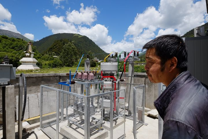 A employee of the power company surveys the new power station near Er Dao Qiao village.