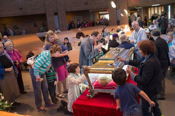 Visitors pray over the remains of Saint Maria Goretti, are displayed at Saint Francis Assisi Church on October 14, 2015 in Or