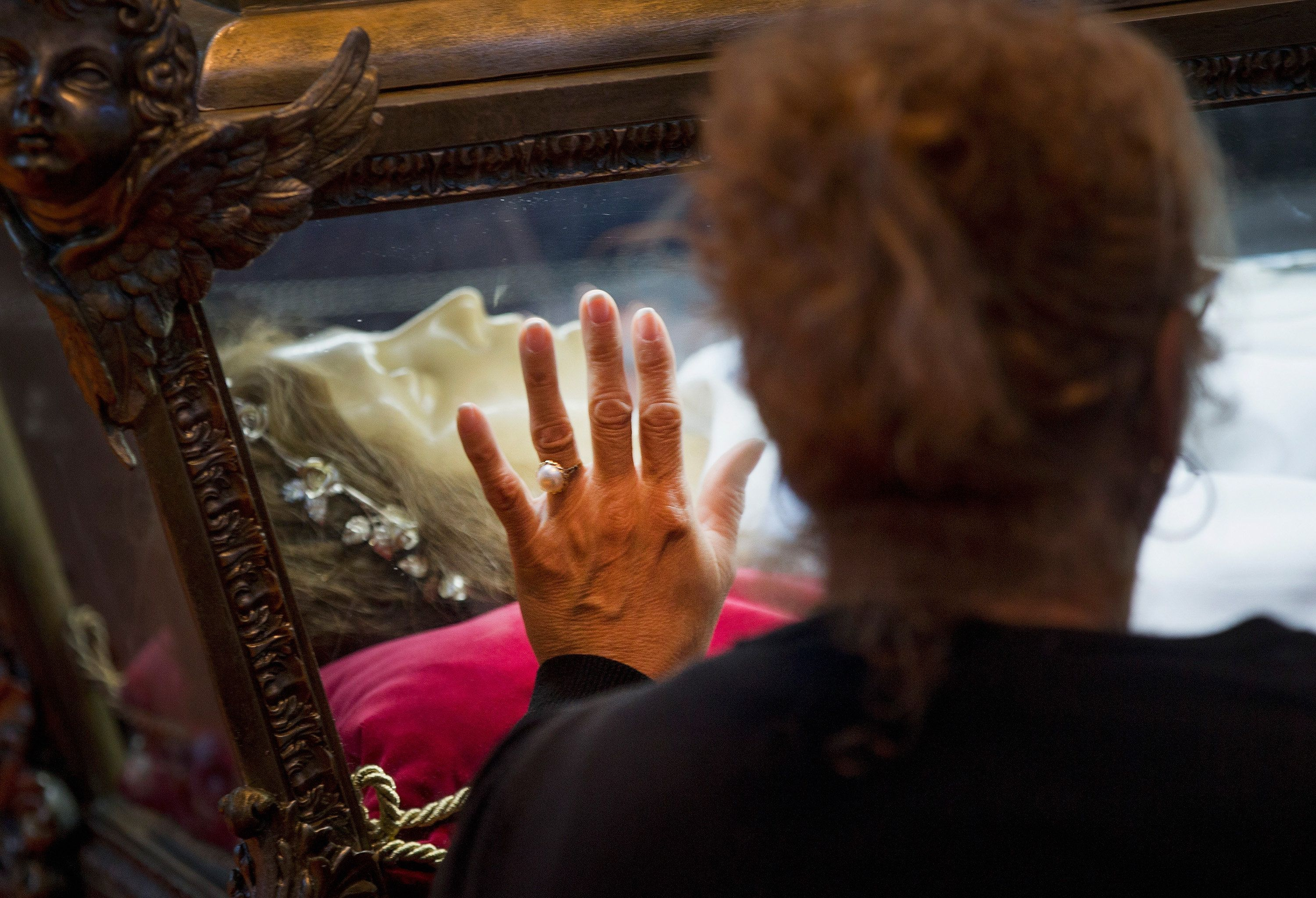 ORLAND PARK, IL - OCTOBER 14: Visitors pray over the remains of Saint Maria Goretti, are displayed at Saint Francis Assisi Church on October 14, 2015 in Orland Park, Illinois. Goretti, the youngest canonized saint in the Catholic Church, was murdered during an attempted rape by Alessandro Serenelli in 1902. The nearly complete skeletal remains are encased in a wax statue and displayed in a glass-sided casket. The remains are on their first ever tour of the United States. (Photo by Scott Olson/Getty Images)
