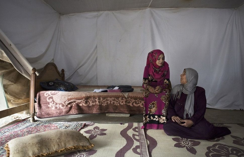 Sumayya, 14, sits with her mother inside their tent shelter in Jeb Janine, Bekaa Valley. The adolescent refused to get marrie