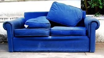 A discarded blue couch on the street