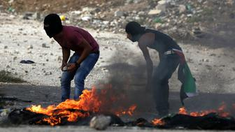 Palestinian protesters gather rocks behind burning tyres during clashes with Israeli security forces at the Hawara checkpoint, south of the West Bank city of Nablus on October 13, 2015. Israeli Prime Minister Benjamin Netanyahu said that Israel would use 'all means' available to end Palestinian violence and that new security measures were planned. AFP PHOTO / JAAFAR ASHTIYEH        (Photo credit should read JAAFAR ASHTIYEH/AFP/Getty Images)