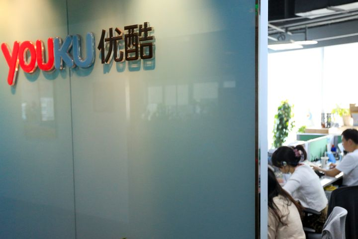 The Youku Tudou Inc. logo is displayed on a wall as employees work at the company's headquarters in Beijing, China. Photograp