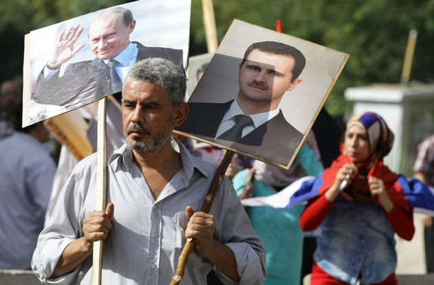 A Syrian man holds up portraits of President Bashar Assad and his Russian counterpart, Vladimir