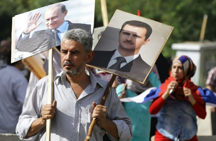 A Syrian man holds up portraits of President Bashar Assad and his Russian counterpart, Vladimir Putin.