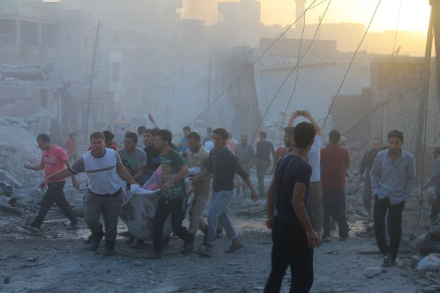 People carry casualties after a reported Russian airstrike in the town Daret Ezza in Aleppo on Oct. 13,