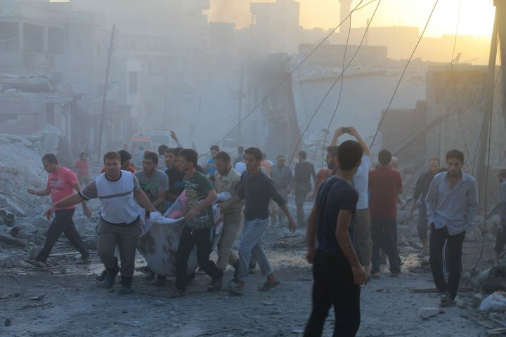 People carry casualties after a reported Russian airstrike in the town Daret Ezza in Aleppo on Oct. 13, 2015.
