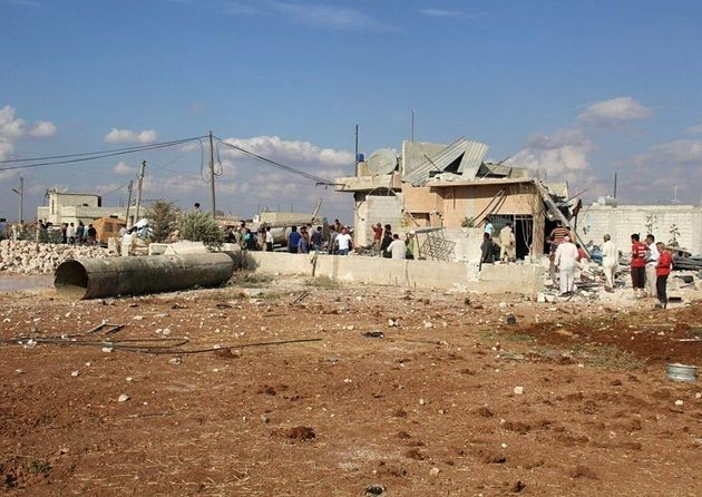 Residents gather outside the destroyed buildings reportedly damaged by Russian airstrikes in Maasaran,...