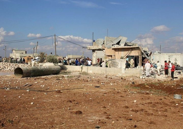 Residents gather outside the destroyed buildings reportedly damaged by Russian airstrikes in Maasaran, Syria, on Oct. 7, 2015
