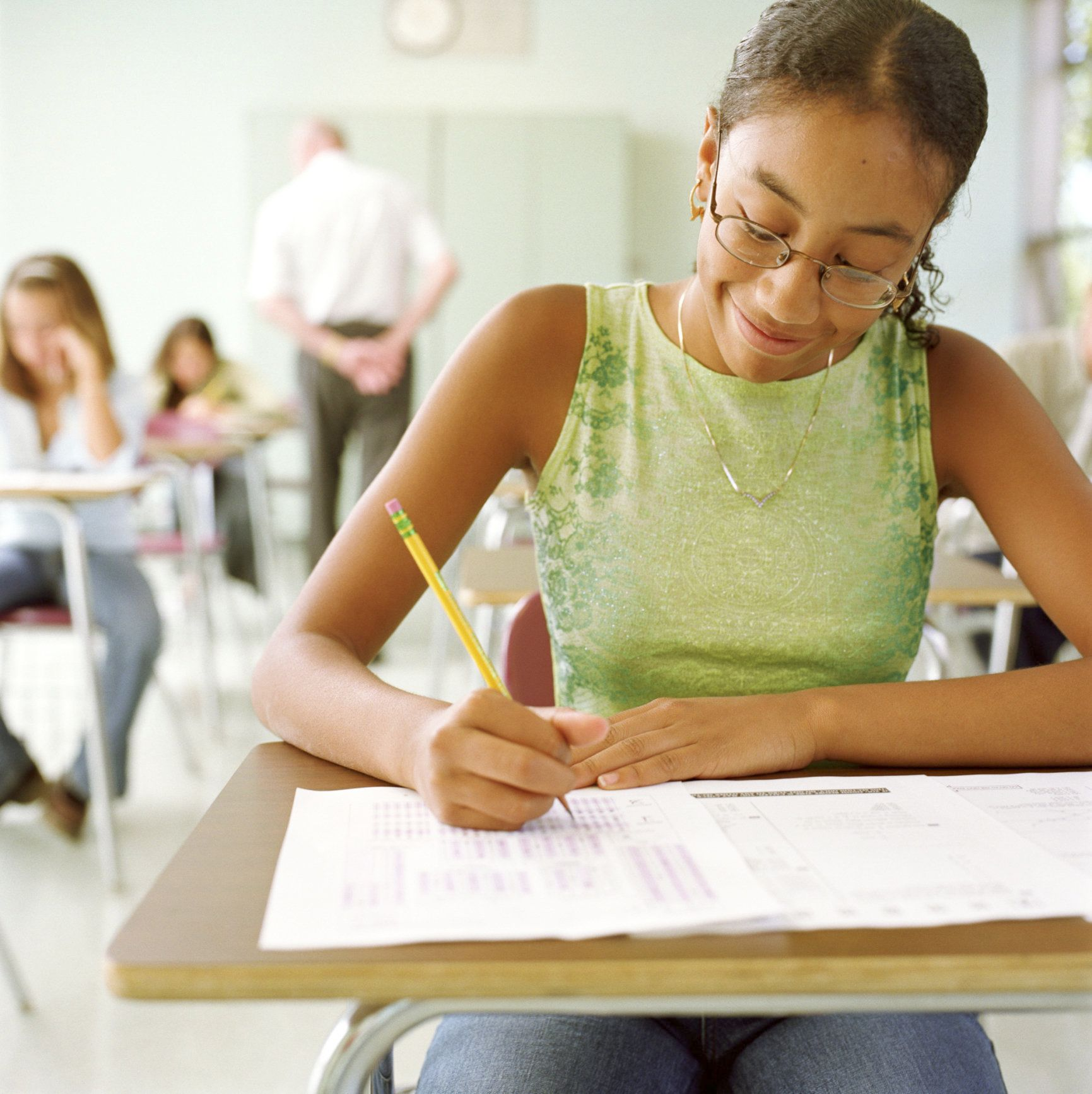 Teenage girl (14-16) taking test in class (focus on right)