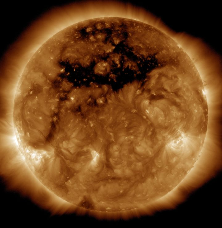 The dark area across the top of the sun in this image is a coronal hole. High-speed solar wind originating from the hole crea
