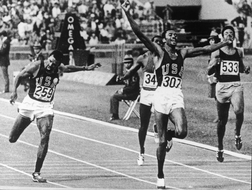 Tommie Smith raises his arms as he crosses the finish line to set a new world and Olympic record at the 1968 Summer Olympics