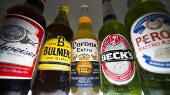 Bottles of beer and cider produced by Belgian-Brazilian group Anheuser-Busch InBev, (Budweiser, Corona and Beck's) and British brewer SABMiller (Peroni and Bulmers) are pictured in London, on October 13, 2015. British brewer SABMiller announced Tuesday it had finally agreed a takeover by Anheuser-Busch InBev, the world's biggest beer producer -- for about $109 billion. Including debt, the cost of buying SABMiller is around $117 billion (£77 billion, 103 billion euros), making it the world's third biggest takeover after two mega mergers across the telecoms sector. AFP PHOTO/JUSTIN TALLIS        (Photo credit should read JUSTIN TALLIS/AFP/Getty Images)