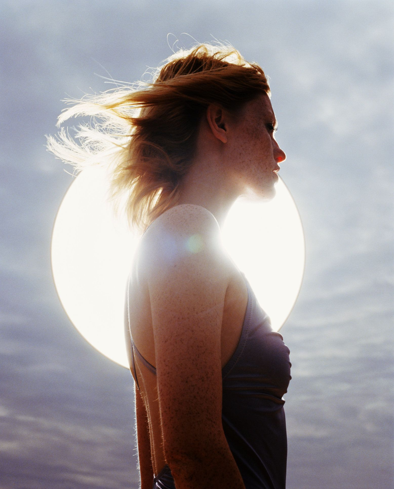 Young woman standing in front of sun, backlit