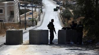 Israeli security stand guard at a roadblock set up on a road close to the Palestinian neighbourhood of Jabal Mukaber in east Jerusalem, on October 15, 2015. Israeli security forces deployed massively in Jerusalem as Jews armed themselves with everything from guns to broomsticks, rattled by a wave of Palestinian attacks that have shaken the country.   AFP PHOTO / AHMAD GHARABLI        (Photo credit should read AHMAD GHARABLI/AFP/Getty Images)