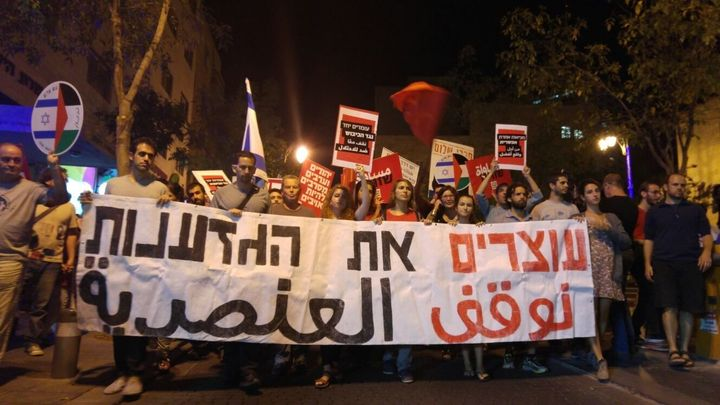 """Israeli and Palestinian activists hold a banner that says """"Stopping Racism"""" in Hebrew and Arabic. Some 2,000 people demonstra"""