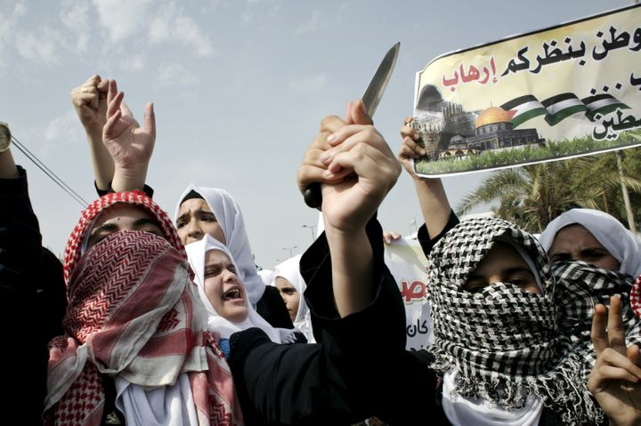 Palestinian students hold a knife during an anti-Israel protest in the city of Khan Yunis in the Southern Gaza Strip, Oct. 18