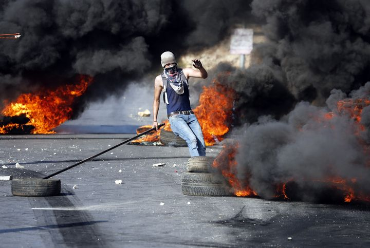 A Palestinian protester kicks burning tires during fierce clashes between Palestinian protesters and Israeli security forces