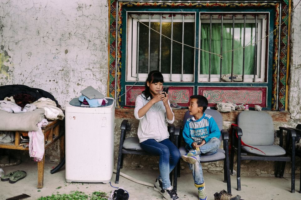 Children in Erdao Qiao village play with a cell phone.