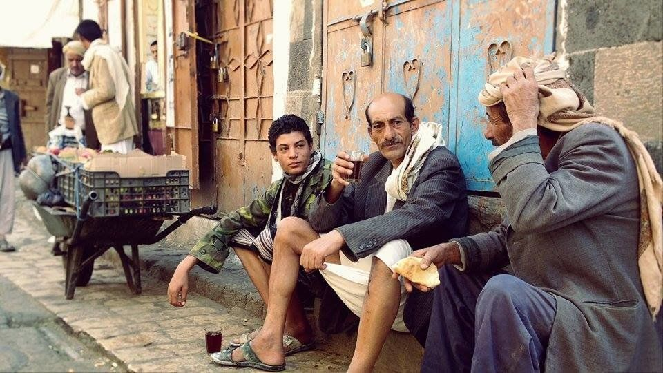 "Three men sit in the old city of Sanaa on April 19, 2015. ""œWe are enjoying our cup of tea under the melody of those stupid j"