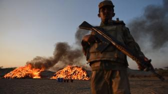A Pakistani soldier of the Anti Narcotics Force stands beside a burning pile of seized drugs on the outskirts of Karachi on October 15, 2015. Pakistani authorities torched tonnes of seized drugs, including heroin, hashish, cocaine, and opium at a ceremony attended by governemt and anti-narcotics officials. AFP PHOTO/ ASIF HASSAN        (Photo credit should read ASIF HASSAN/AFP/Getty Images)