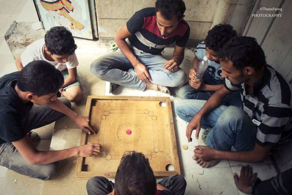 Young people play a game on Jamal Street in Sanaa on June 15, 2015.