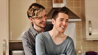 Two young men smiling and holding one another.