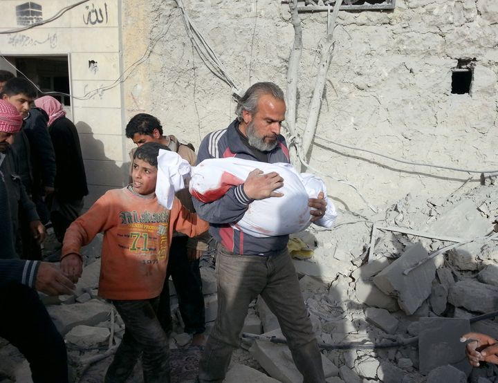 A Syrian man carries the body of a child after a barrel bomb attack by Syrian regime helicopters in Aleppo, Syria, on March 6