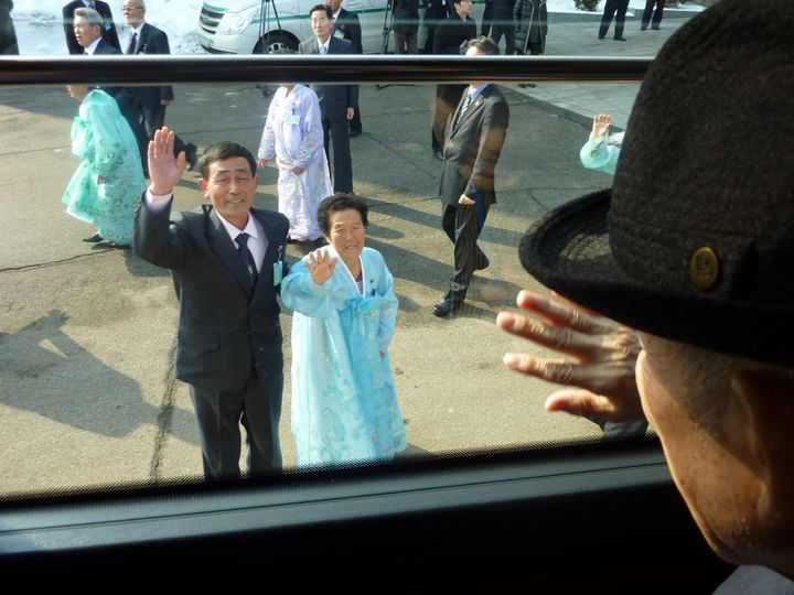 South Korean Kim Se-rin waves goodbye from a bus to his North Korean sister and nephew as he leaves a 2014 family reunion eve