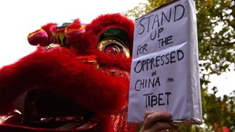 LONDON, ENGLAND - OCTOBER 20:  Pro-China supporters perform a dragon dance infront of a supporter of Amnesty International who is holding a sign with the slogan 'stand up for the oppressed in China and Tibet'. Amnesty International are protesting against claims of a deterioration in human rights and censorship of the internet and media during a state visit by Chinese President Xi Jinping on October 20, 2015 in London, England. The President of the People's Republic of China, Mr Xi Jinping and his wife, Madame Peng Liyuan, are paying a State Visit to the United Kingdom as guests of The Queen. They will stay at Buckingham Palace and undertake engagements in London and Manchester. The last state visit paid by a Chinese President to the UK was Hu Jintao in 2005.  (Photo by Ben Pruchnie/Getty Images)